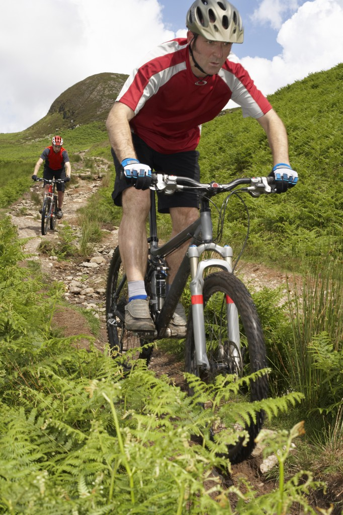 Two cyclists on countryside track against hill and sky