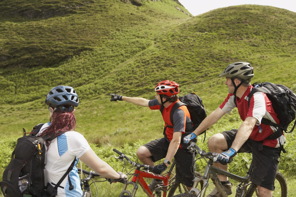 shutterstock_Three cyclists with bikes on lush landscape